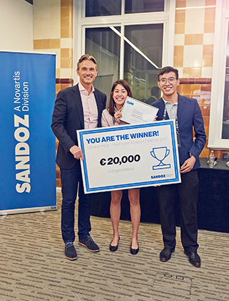 Kyla Relucio and Joel Alejandro receive their prize from Richard Francis, Sandoz Global CEO