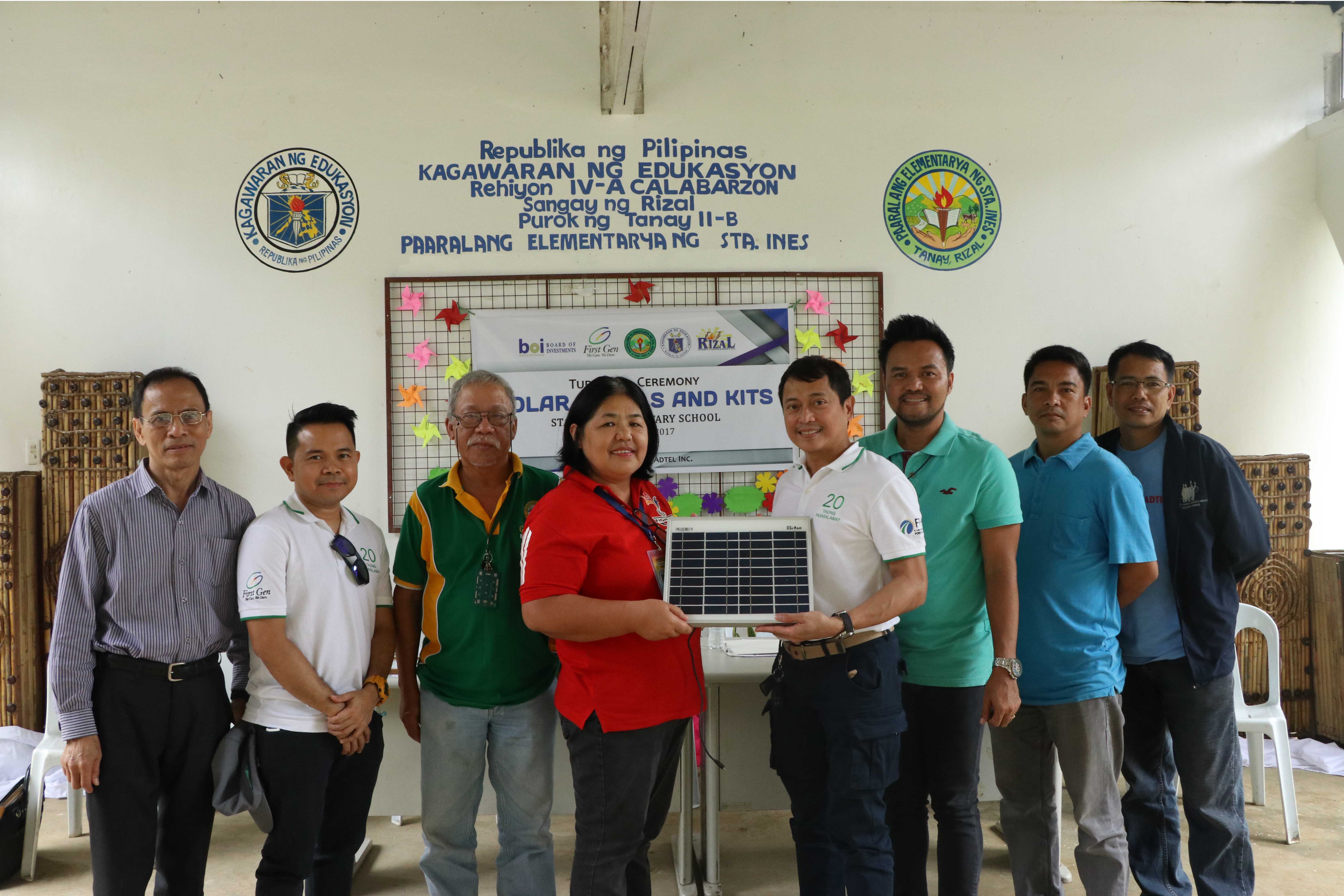 Jerome Cainglet (5th from left), First Gen vice president, presents a sample of a solar panel to Adoracion Valdez  (4th from left), head teacher of Santa Ines Elementary, during  the turnover of a solar power system First Gen donated to the school. Also in photo are (l-r) Nestor Arcansalin, BOI director; Michael Reapor, First Gen assistant vice president; Gil Zubiaga, Brgy.Santa Ines chairman; Buddy Chester Repia of theDepartment of Education; and Ariel Abejuro with Reynaldo Reyes of Adtel