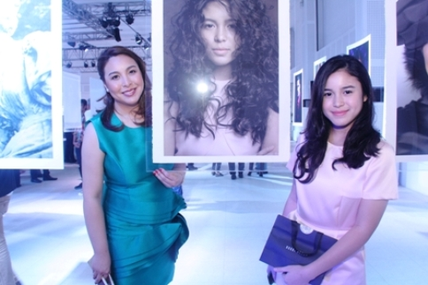 Marjorie and Claudia pose beside Claudias photo in Rituals