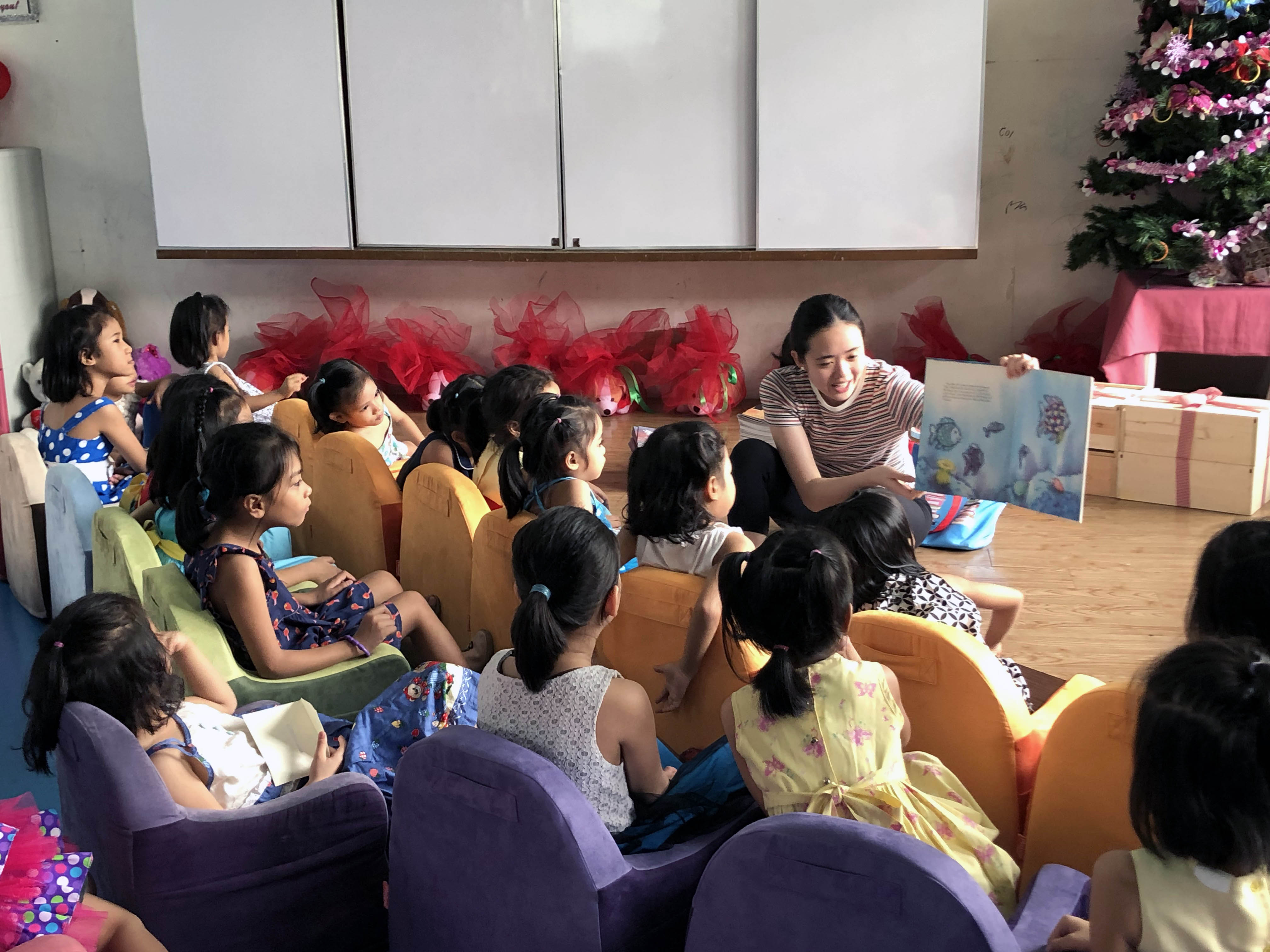 Alexis Lopez (right) reads to the children at White Cross Orphanage