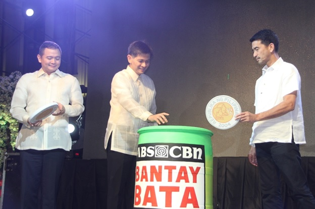 Mayor Joet Garcia of Balanga, Bataan drops a big ten peso coin in a giant Bantay Bata coin bank with Governor Abet Garcia (left) and Vice Mayor Noel Valdecanas (right) during Balanga Bataan's 14th Cityhood Anniversary