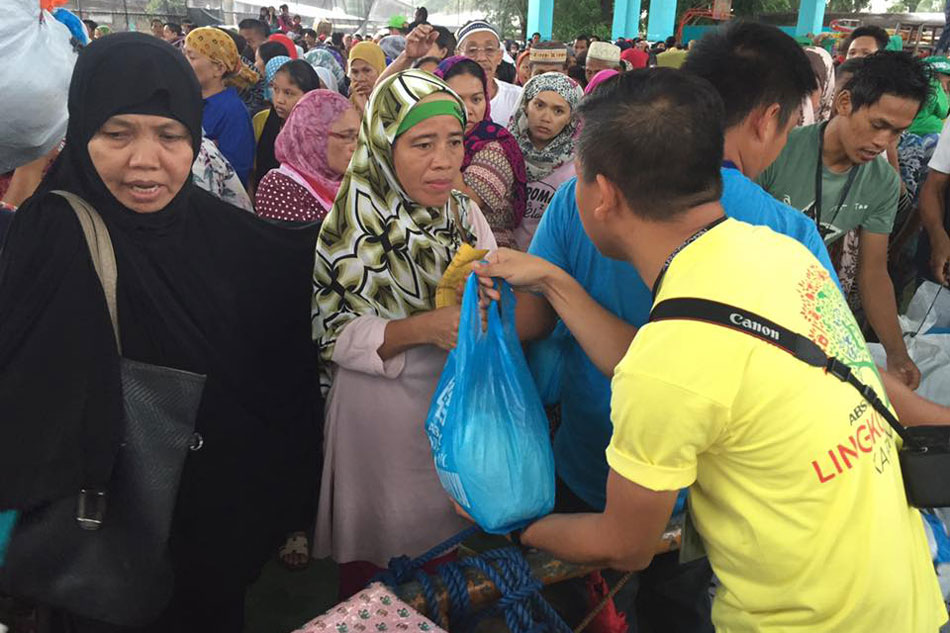 A woman receives a food pack in BaloiLanao Del Norte