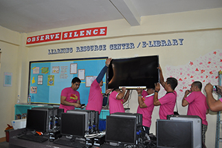 The volunteers set up the TV set and ABS-CBN TVplus box at the Learning Resource Center