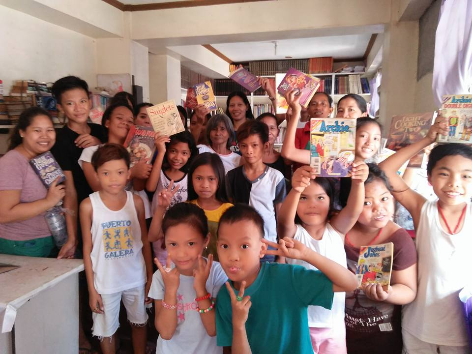 Beneficiaries from San Isidro Labrador Parish happily show off the books they borrowed from the portable library