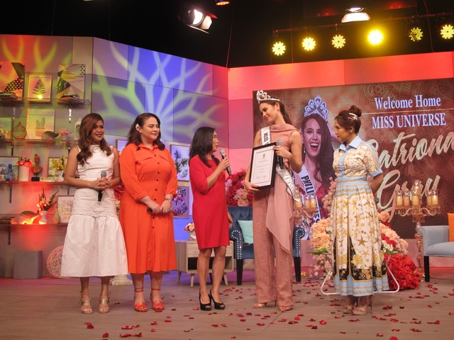 "KCFI president Rina Lopez-Bautista (center) presents the citation to Miss Universe 2018 Catriona Gray as ""Magandang Buhay"" hosts Melai Cantiveros, Karla Estrada and Jolina Magdangal look on"