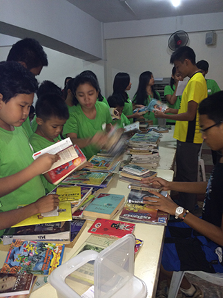 PAAFI beneficiaries choose books to borrow from the portable library