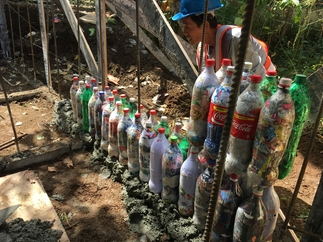 A worker prepares a wall of ecobricks  fort