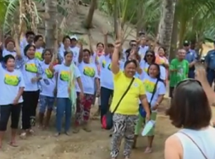ALKFI executive director Gina Lopez (at right, back to camera) pumps up community members in Guimaras