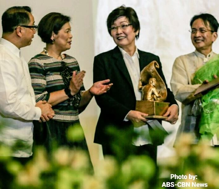 ABS-CBN News anchor and former Bantay Bata program director Tina Monzon Palma receives the Gawad Plaridel from UP officials