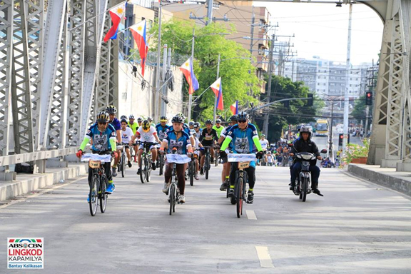 'PadyaKantahan' bikers cross Quezon Bridge on their way to Paco