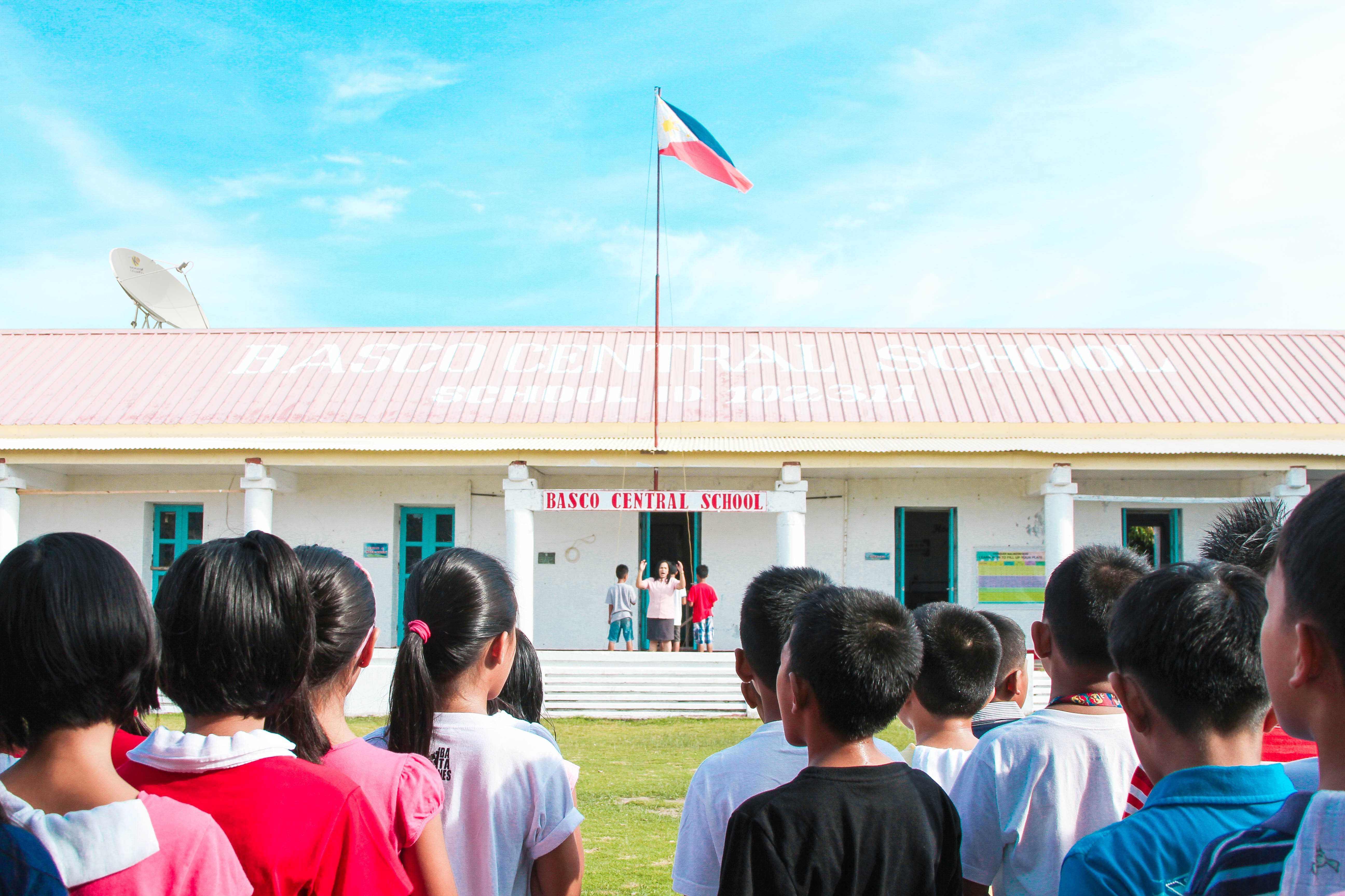 "Students of Basco Central School hold their heads high during a flag ceremony. The school is one of the four ""Gift of Knowledge"" beneficiaries in partnership with SKYcable"