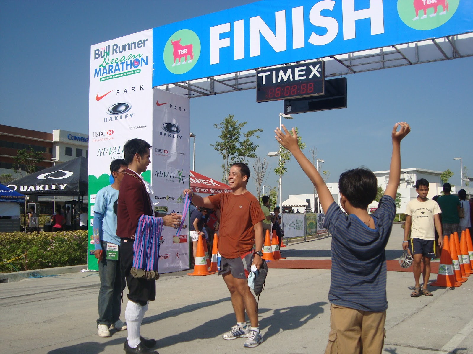 In this 2010 photo, De Lima (center) is greeted at the finish line of his first marathon by son Marcel (right)